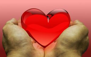 two hands holding a red glass heart